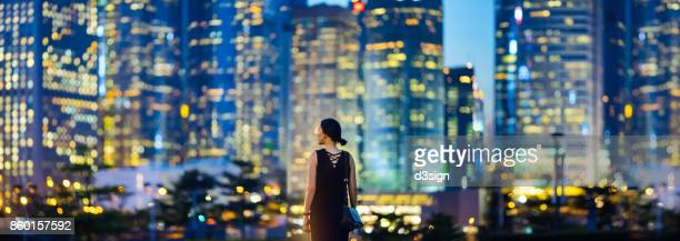 young businesswoman standing against illuminated cityscape of hong kong metropolitan at night - panoramic stock pictures, royalty-free photos & images