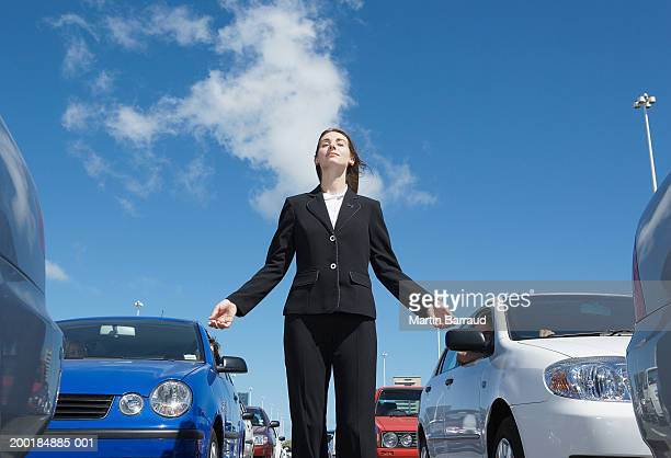 Young businesswoman standing amongst traffic jam, meditating