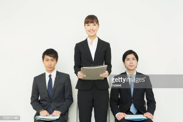 Young businesswoman standing and talking between businessmen