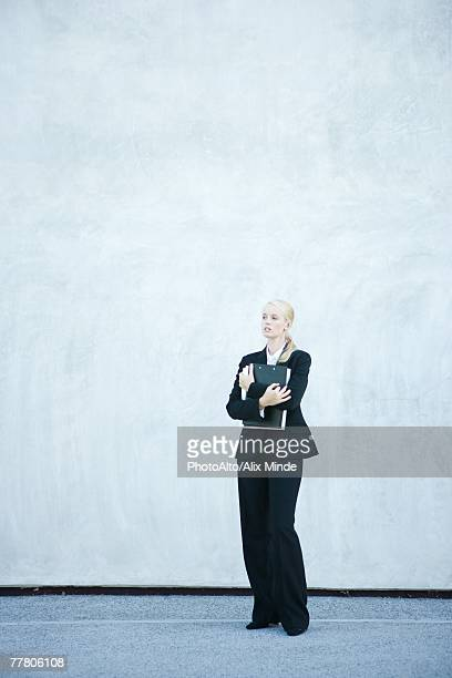 Young businesswoman standing, arms folded, full length