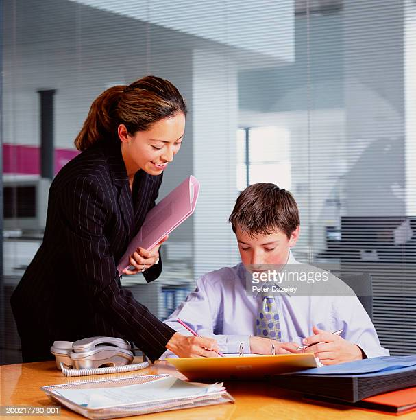Young businesswoman standing by teenage boy (14-16) trainee in office