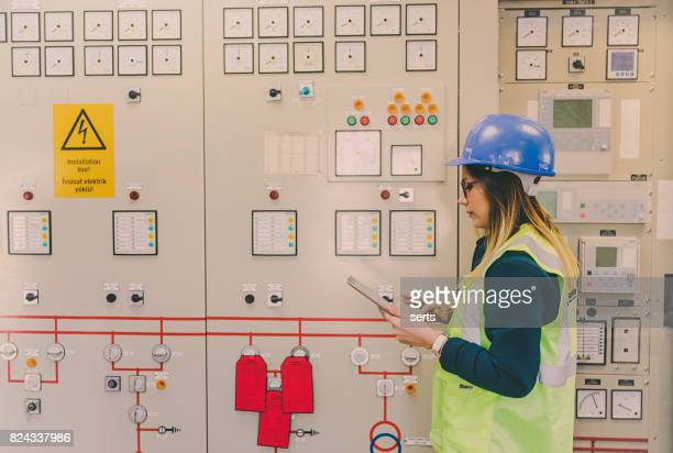 Young businesswoman standing in front of the control panel in the control room