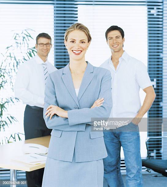 Young businesswoman standing in office, arms folded, smiling, portrait