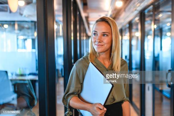 young businesswoman standing in office hallway with laptop - vanishing point stock pictures, royalty-free photos & images