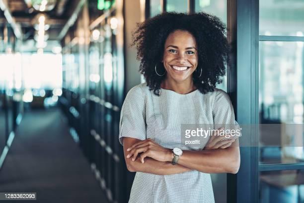 jovem empresária parada no corredor - pessoa de negócios - fotografias e filmes do acervo