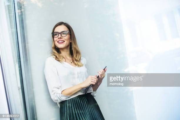 Young businesswoman standing next to the window with digital tablet