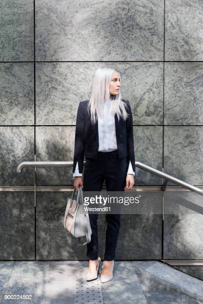Young businesswoman standing outdoors looking around
