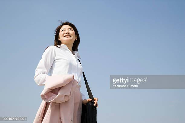 Young businesswoman standing outdoors with bag, low angle view