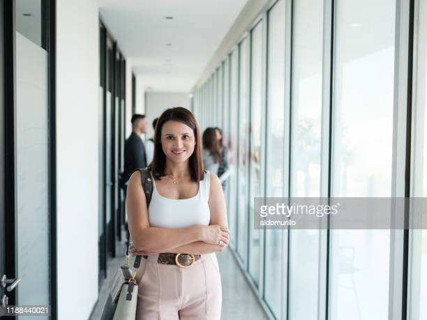 young businesswoman standing with arms crossed and smiling - medium shot stock pictures, royalty-free photos & images