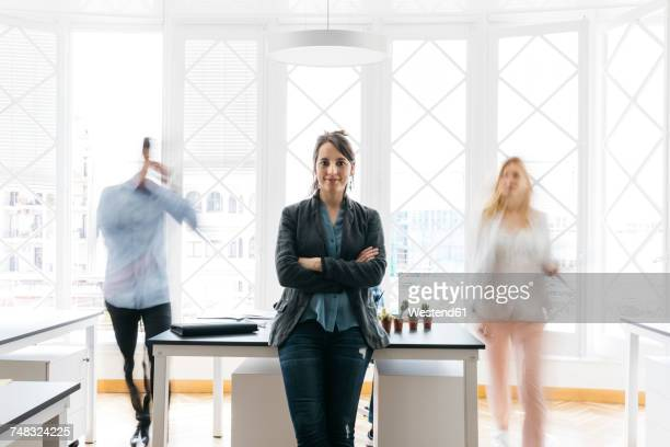 Young businesswoman standing with arms crossed in office while colleagues are moving