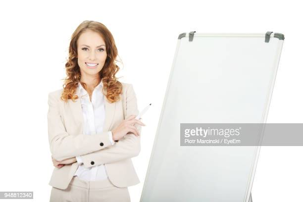 Young Businesswoman Standing With Blank Whiteboard Against White Background
