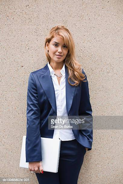 Young businesswoman standing with laptop by wall, portrait