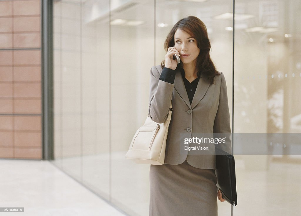 Young Businesswoman Stands by a Glass Building, Talking on Her Mobile Phone : Stock Photo
