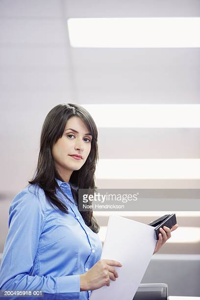 Young businesswoman stapling documents, portrait, side view