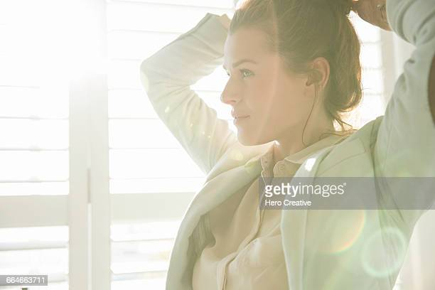 young businesswoman styling hair in sunlit bedroom - morning ストックフォトと画像