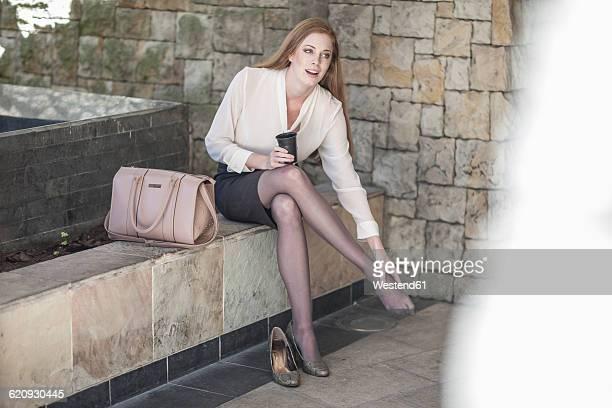 Young businesswoman taking a break, sitting on bench rubbing feet