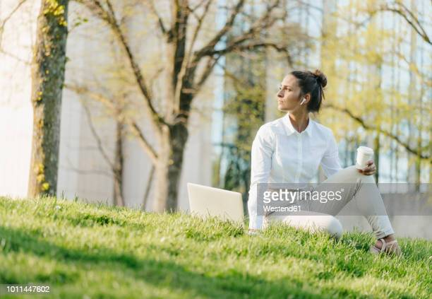 young businesswoman taking break, using laptop, sitting in grass and drinking coffee - よそいきの服 ストックフォトと画像