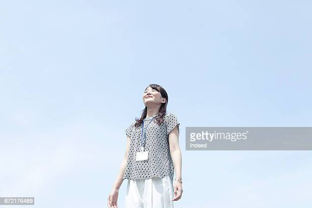 Young businesswoman taking deep breath under sky