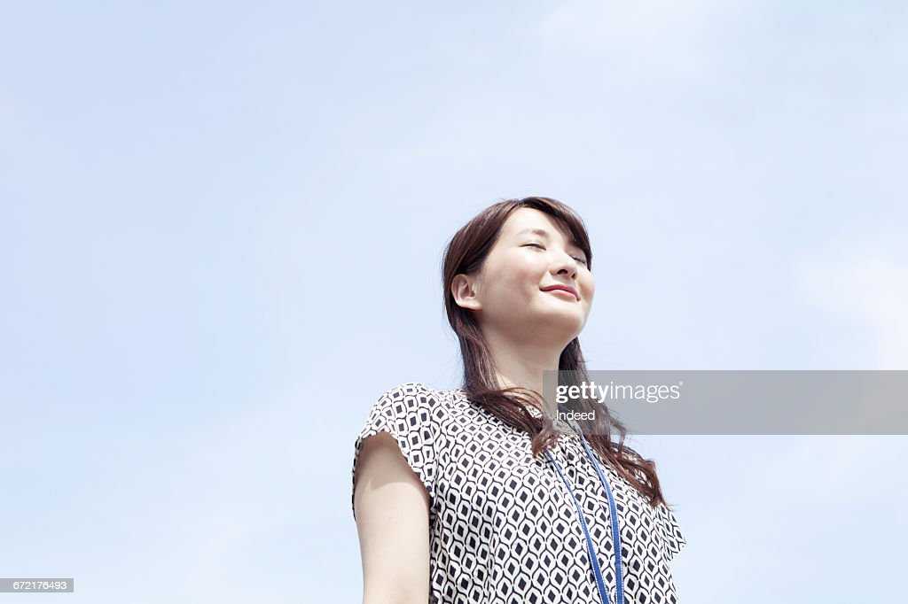 Young businesswoman taking deep breath under sky : Stock Photo