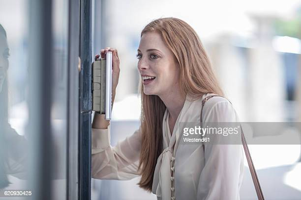 young businesswoman talking at intercom - intercom stock pictures, royalty-free photos & images