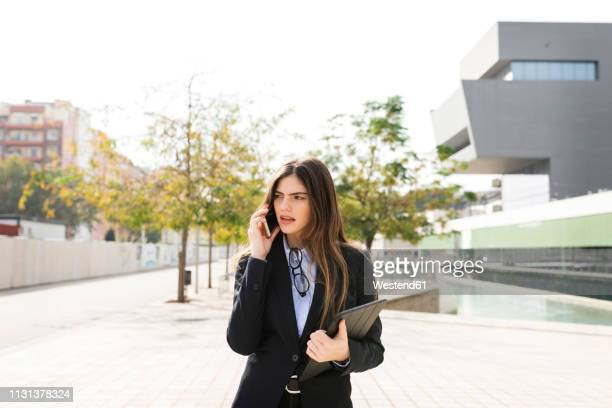young businesswoman talking on cell phone in the city - ビジネスウェア ストックフォトと画像