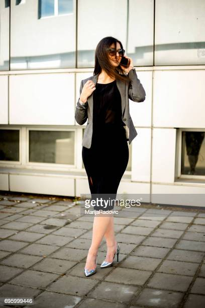 young businesswoman talking on mobile phone - black blazer stock pictures, royalty-free photos & images