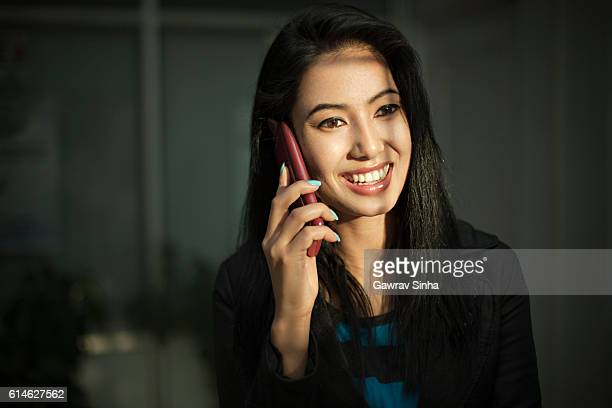 Young businesswoman talking on smart phone in morning window light.