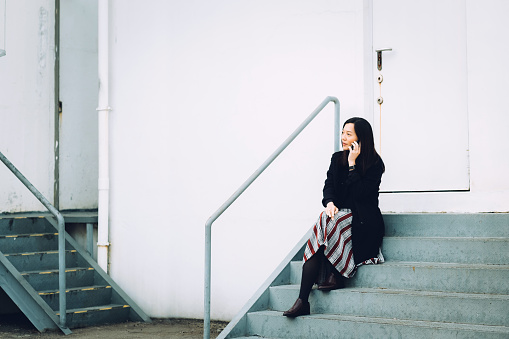 Young businesswoman talking on smartphone while sitting on stairs in city - gettyimageskorea