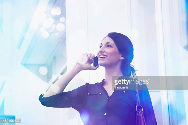 Young businesswoman talking on smartphone with lights coming out of it