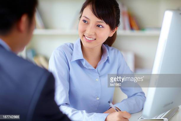 young businesswoman talking to customer in office