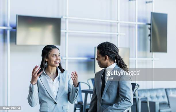 young businesswoman talking to male coworker - minority groups stock pictures, royalty-free photos & images
