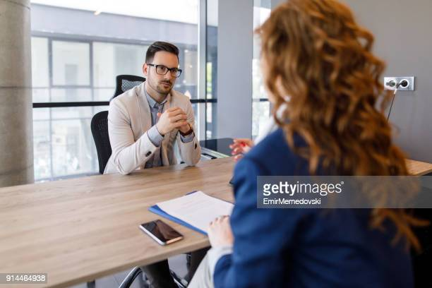 Young businesswoman talking to prospective employer at job interview