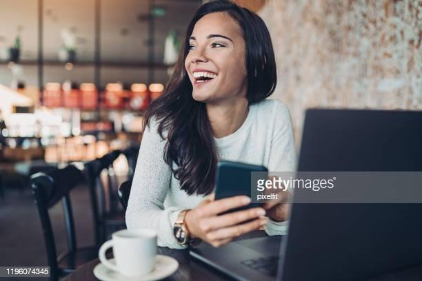 a mulher de negócios nova que texting em um restaurante - independência - fotografias e filmes do acervo