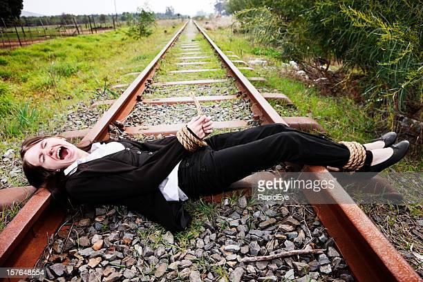 young businesswoman tied to railroad track screams in terror - bound woman stock photos and pictures