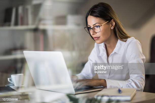 young businesswoman typing an e-mail on laptop at home office. - businesswoman stock pictures, royalty-free photos & images