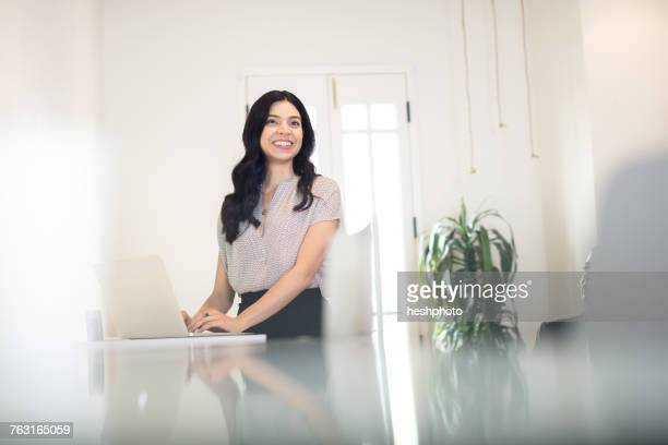 young businesswoman typing on laptop at desk - heshphoto stock pictures, royalty-free photos & images