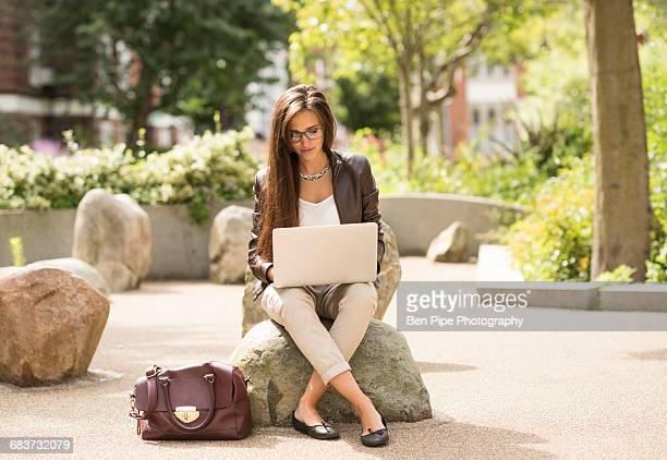 young businesswoman typing on laptop in city park - smart casual stock pictures, royalty-free photos & images