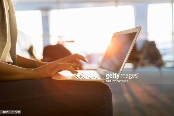 young businesswoman uses laptop in airport - computer keyboard stock pictures, royalty-free photos & images