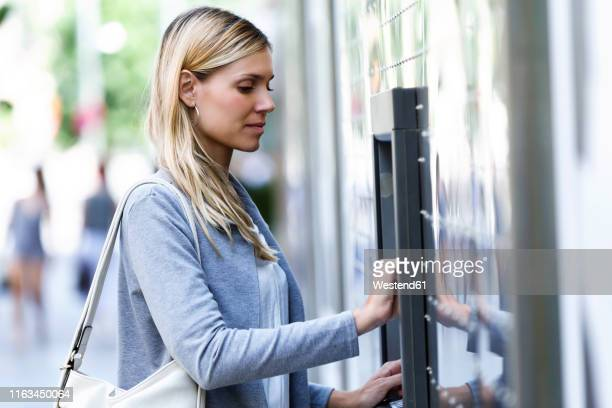 young businesswoman using a credit card to withdraw money on a cash machine outdoors - ショルダーバッグ ストックフォトと画像
