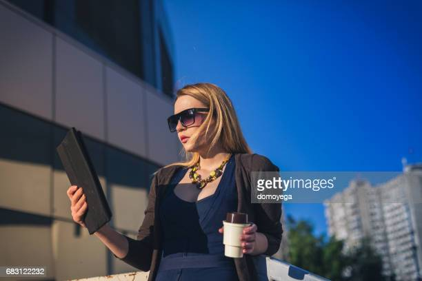 young businesswoman using a laptop outdoors on a spring day - taken on mobile device stock photos and pictures