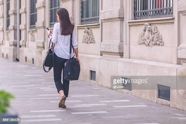 jeune femme d'affaires à l'aide de téléphone portable sur sa façon de travailler - femme brune de dos photos et images de collection