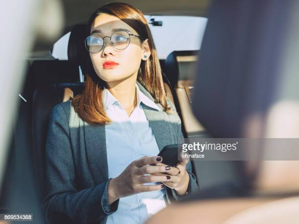 young businesswoman using cellphone on car backseat