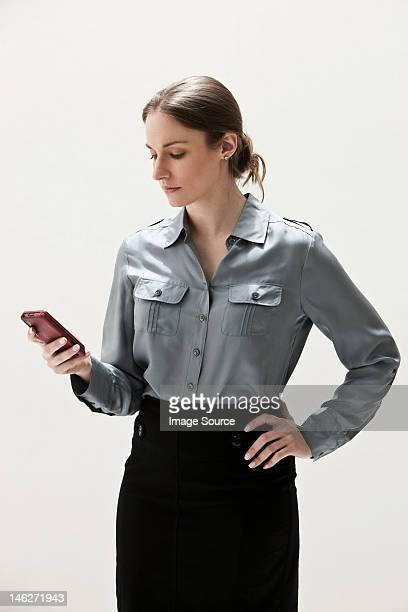 young businesswoman using cellphone, studio shot - 若い女性一人 ストックフォトと画像