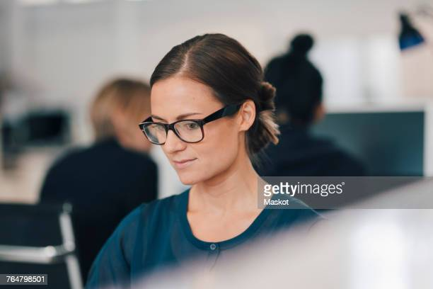Young businesswoman using computer at office