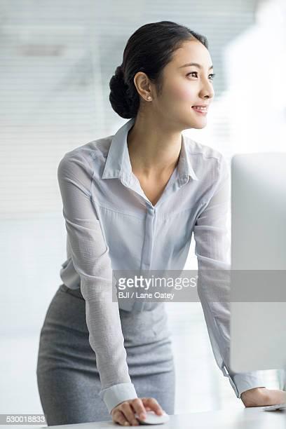 young businesswoman using computer in office - trabalhadora de colarinho branco imagens e fotografias de stock