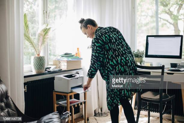 young businesswoman using computer printer at home office - 印刷機 ストックフォトと画像