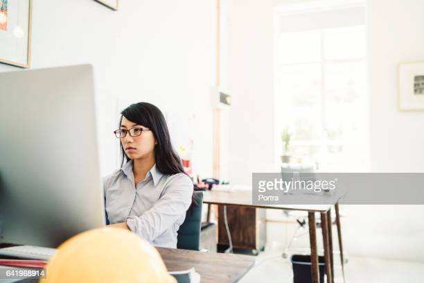 Young businesswoman using desktop computer