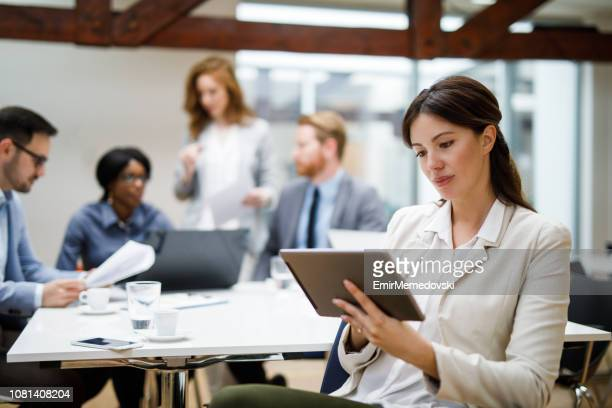 Young businesswoman using digital tablet and analyzing business report