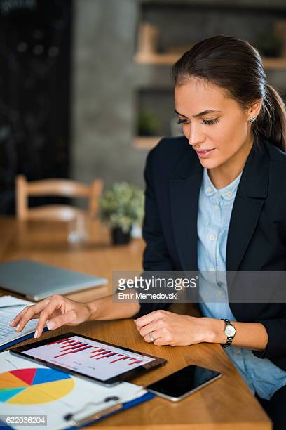 young businesswoman using digital tablet and analyzing business report. - digital marketing stock photos and pictures