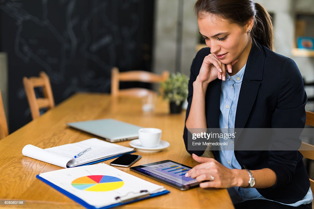 Young businesswoman using digital tablet and analyzing business report. : Stock-Foto